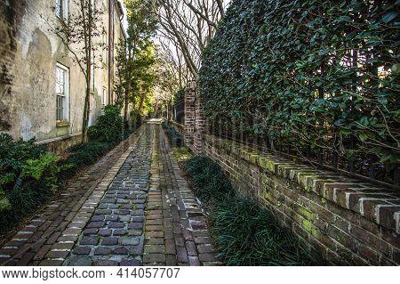 Narrow Brick Lined Historic Alley Way In Downtown Charleston, South Carolina. The City Of Charleston
