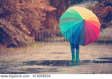 Child Walking In Wellies In Puddle On Rainy Weather. Boy Holding Colourful Umbrella Under Rain In Su