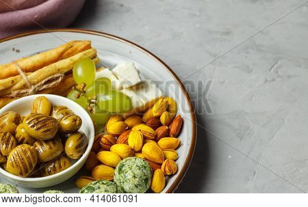 A Plate Of Tapas On A Gray Stone Background With Copy Space , Close-up.dried Olives, Pistachios With