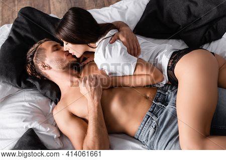 Top View Of Sensual Woman In T-shirt And Panties Kissing Sensual Man On Bed.