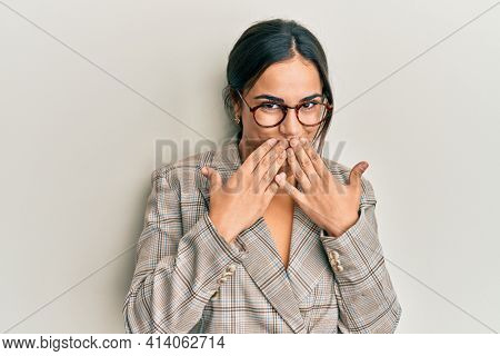 Young brunette woman wearing business jacket and glasses laughing and embarrassed giggle covering mouth with hands, gossip and scandal concept