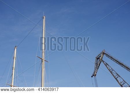 The Yacht's Masts And An Old Crane Against The Blue Sky With The Moon With Space For Text.