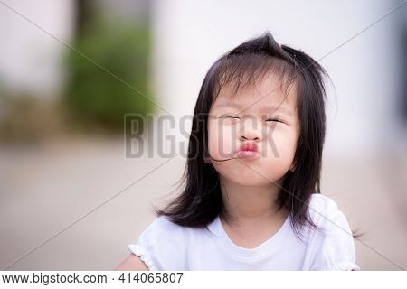 Cute Child Shows A Cheeky Face, Wrapping His Mouth Black-haired Asian Children Are Happy. Kids Play