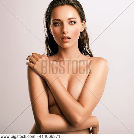 Young beautiful woman with healthy perfect body. Tanned body of an attractive white girl which posing at studio. Brunette woman hiding her naked body with hands.