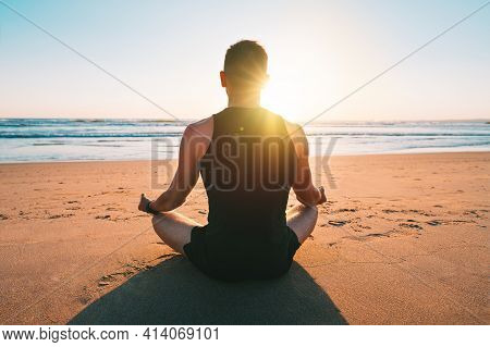 Healthy Man Practicing Yoga And Meditates On The Beach With Ocean View At Sunset Or Sunrise. Sitting