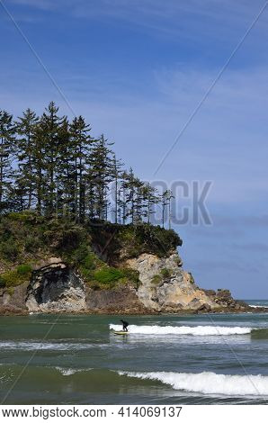 Paddle Boarder Riding  A Wave In Sunset Bay State Park, Oregon