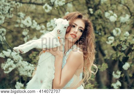 Woman With Goat In Blossom Forest. Nymph In A Blossom Forest With Lamb. Beautiful Girl, Sensual Youn