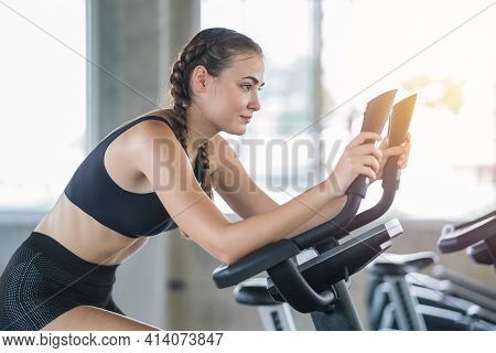 Beautiful Sport Woman Working Out On Exercise Bike At Sport Health Club
