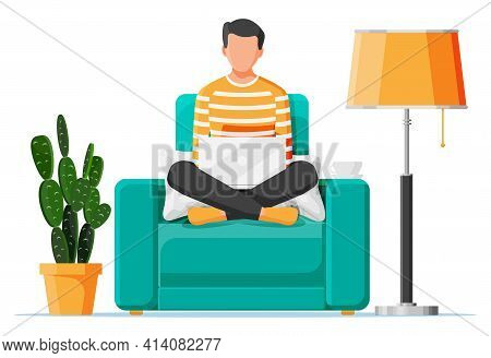 Freelancer Boy In Armchair Works At Home. Comfortable Workplace Interior With Plant, Floor Lamp. You