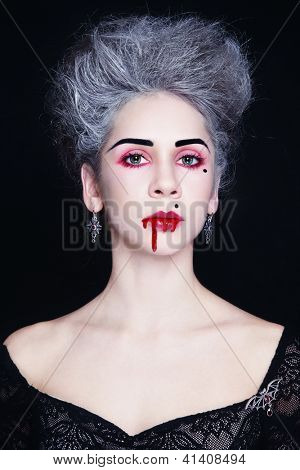 Young beautiful stylish gothic woman with vintage hairdo and bloody mouth