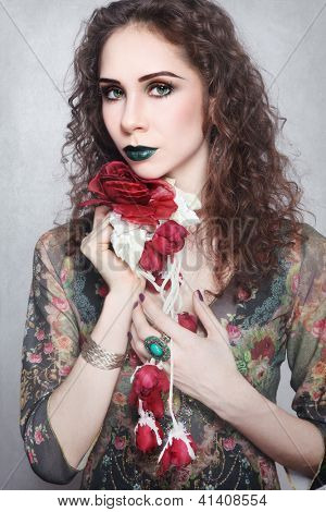 Portrait of young beautiful woman with fancy make-up and silk flower in her hands, on vintage grainy damaged background