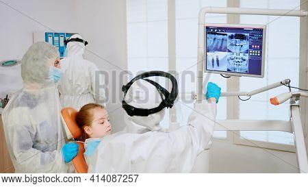 Stomatologist In Coverall Explaining Dental Problem Using Digital Monitor