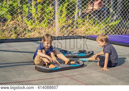 Happy Boys On A Soft Board For A Trampoline Jumping On An Outdoor Trampoline, Against The Backdrop O