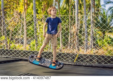 Happy Boy On A Soft Board For A Trampoline Jumping On An Outdoor Trampoline, Against The Backdrop Of