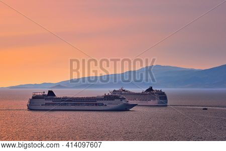 Two Big Tourist Cruise Liners Manoeuvre In Harbor. Beautiful Sunset Sky And Distant Hazy Islands. Se