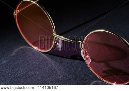 Close-up Of Glasses With Pink Lenses On A Dark Background. Selective Focus. Minimal Design With Copy