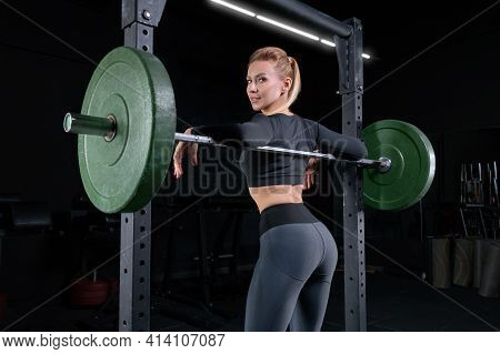 Leggy Girl Posing In The Gym. She Leaned On The Barbell. The Concept Of Sports, Bodybuilding, Fitnes