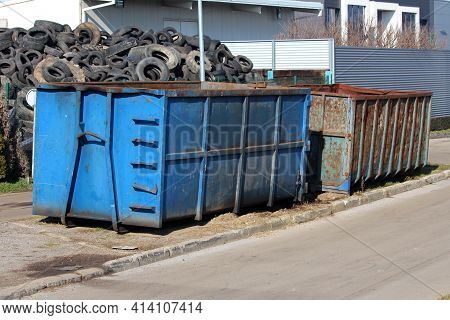 Large Pile Of Used Car Tyres Behind Two Heavily Used Industrial Partially Rusted Strong Blue Metal R