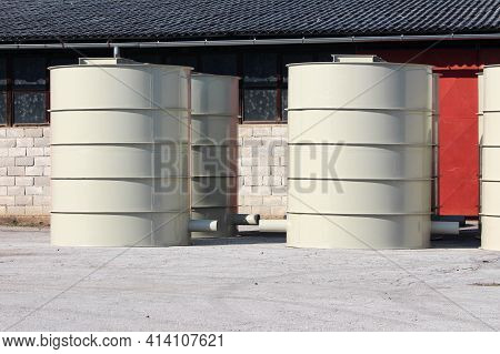 Rows Of Brand New Freshly Painted Metal Water Tanks With Large Covers On Top And Metal Pipe On Side