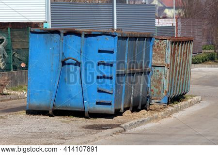 Two Heavily Used Large Industrial Partially Rusted Strong Blue Metal Recycling Containers Left On Si
