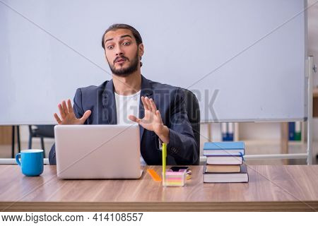 Young male teacher in tele-studying concept