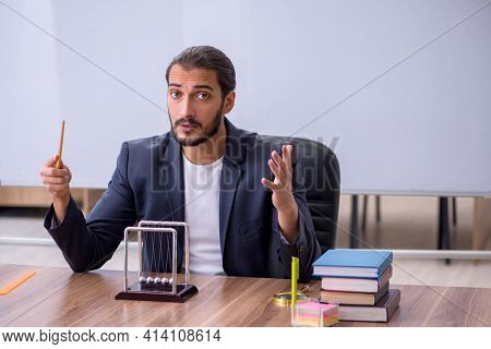 Young male teacher physicist in the classroom