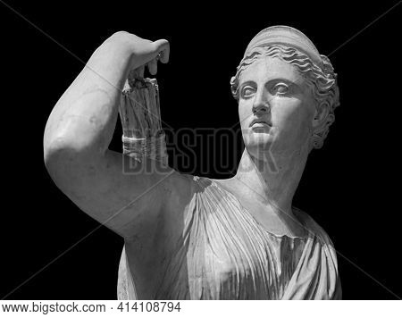Classic white marble statuette Diana of Versailles isolated on black background. Scilpture of huntress.