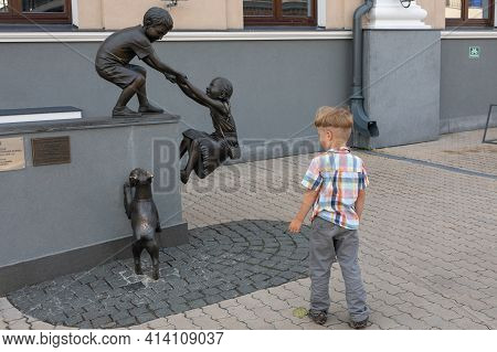 Little Boy Carefully Examines Sculpture Of Children Helping Each Other And Dog. Sculptural Compositi