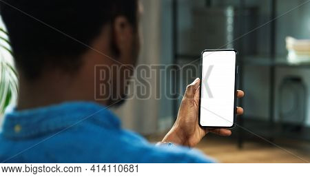 Close Up Of African American Man Holding New Black Smartphone With Blank Screen In Hands. Mobile Pho