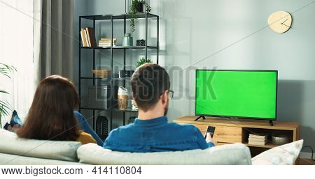 Back View Of Young Couple Wife And Husband Watching Tv With Chroma Key Choosing Program While Restin