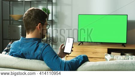 Caucasian Man In Glasses Sitting On Sofa In Modern Room In House Watching Tv With Green Screen And T