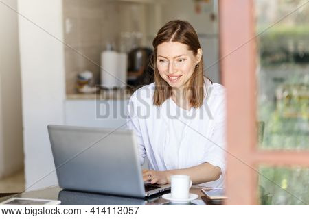 Happy Young Woman. Remote Work On A Laptop Computer From Your Favorite Kitchen At Home. White T-shir