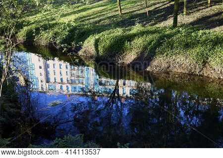 Building Reflected In The Water Of A River In A Forest