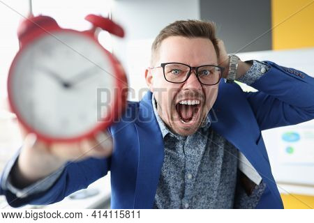 Young Man Holding Alarm Clock And Shouting