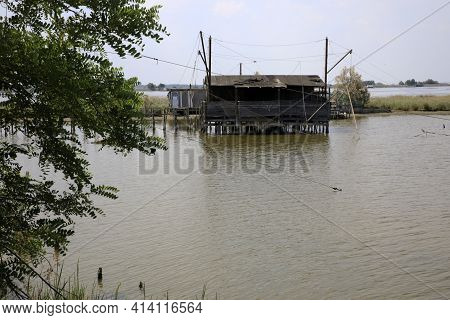 Po River (fe),  Italy - April 30, 2017: An Old Fisherman's House With Nets On Po River, Delta Region