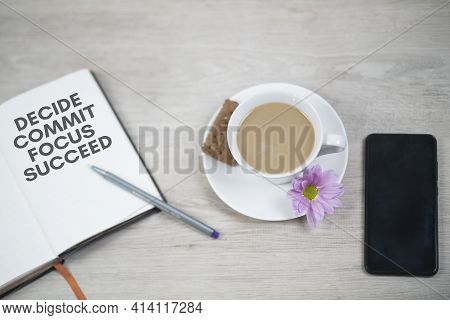 Business Motivational Words - Decide Commit Focus Succeed. Written On Open Book With Pen, Cup Of Cof