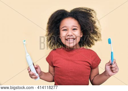 Smiling African American Little Girl Holds Manual And Electric Sonic Toothbrushes, Isolated On Beige
