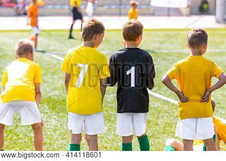Boys In Yellow Soccer Jerseys With Player Numbers On Back. Football Team Standing On Sideline. Group