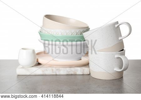 Different Dishware And Marble Board On Grey Table