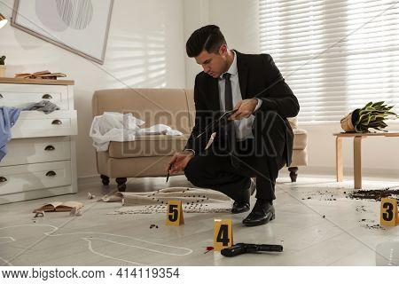 Investigator In Black Suit Examining Crime Scene