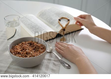 Woman With Bible Having Dinner At Home, Closeup. Great Lent Season