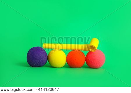 Clown Noses And Party Blower On Green Background