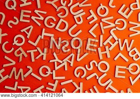 Top View Closeup Detail Macro Of Many Wooden Cut Small Alphabet Letters On Orange Background