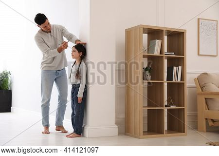 Father Measuring Height Of His Daughter Near Wall At Home