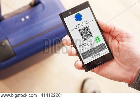 Mobile phone in hand  with digital green certificate of vaccination covid-19. Phone screen with information about the presence of vaccinations and antibodies to covid the background of a suitcase  bag