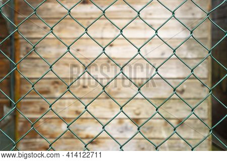 Steel Green Fence Mesh Netting And Old Plank Wooden Wall In Blur On The Background