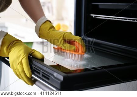 Woman Cleaning Oven Door With Baking Soda In Kitchen, Closeup
