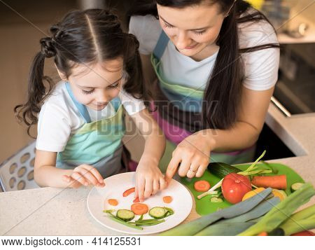 Cute Mom And Little Girl Making Funny Face From Vegetables In Kitchen. Mother And Her Daughter Cooki
