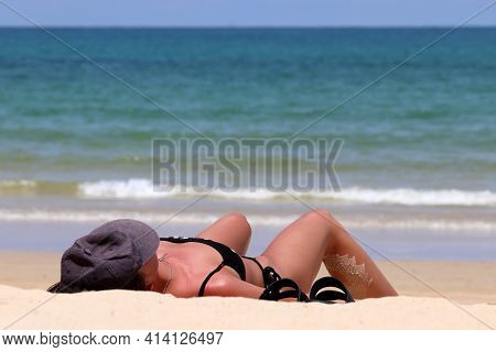 Woman In Bikini Lying And Tanning On A Sandy Beach On Sea Background, Tanned Skin Is Covered By Sand