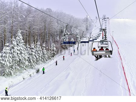 Skiers And Snowboarders Are Lifting On Ski-lift. Downhill Ride. Adventure Skiers Season. Skiing And